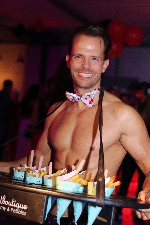 Sexy butler deelt frites uit op een bedrijfsfeest